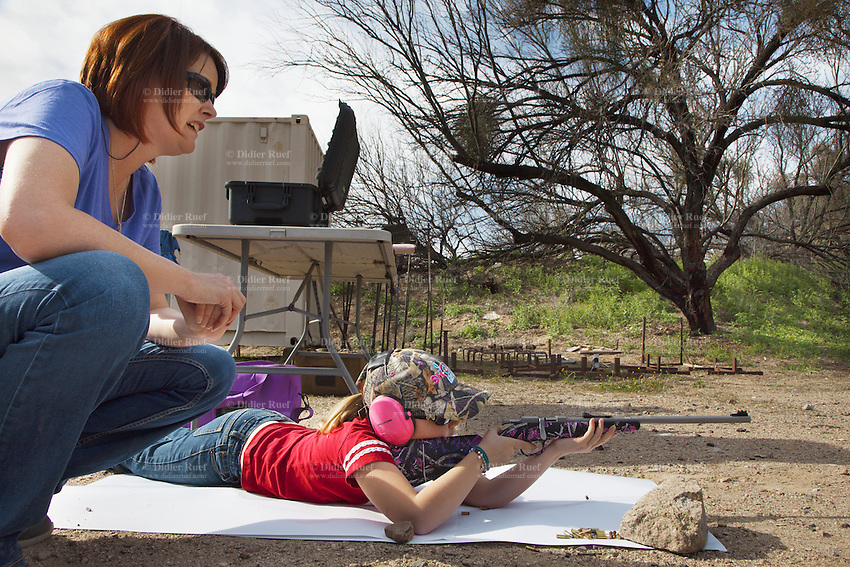 USA. Arizona state. Kearny town. Copper Basin Sportsmen's Club. Marti Stonecipher with her daughter Dakota, 8 years old. Marti is a certified instructor NRA (National Rifle Association) Basic Pistol, NRA PPITH, NRA Range Safety Officer. Dakota is training her shooting skills with her Henry Mini Bolt .22 - Single Shot Bolt Action Rifle. The rifle helps young shooters be successful on shots, thanks to the Williams Fire fiber-optic sights that make it easy to aim and the wraparound checkering that offers a firm grip, even for little hands. The rifle is a single-shot, European-style bolt action and has a manual safety switch. Copper Basin Sportsmen's Club is a membership Range complex which purpose is to promote the sport of shooting and providing a safe, fun, family oriented environment. A firearm is a portable gun, being a barreled weapon that launches one or more projectiles often driven by the action of an explosive force. Most modern firearms have rifled barrels to impart spin to the projectile for improved flight stability. The word firearms usually is used in a sense restricted to small arms (weapons that can be carried by a single person). The right to keep and bear arms is a fundamental right protected in the United States by the Second Amendment of the Bill of Rights in the Constitution of the United States of America and in the state constitutions of Arizona and 43 other states. 29.01.16 © 2016 Didier Ruef