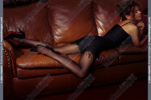 Sensual portrait of a beautiful sexy woman lying on a brown leather couch wearing a short black dress, black stockings and high heel shoes