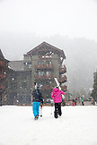 USA, Colorado, Aspen, skiers at the Highlands Mountain base walk in the falling snow, Highlands Ski Resort