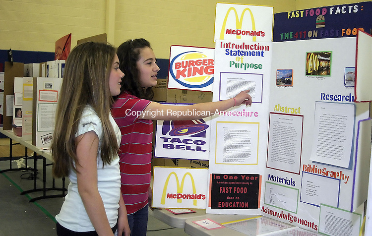NAUGATUCK, CT -30 MAY 2007 - -053007DA01--  Ayse Hursid, points the purposes of her eye catching, science fair project that she teamed up with Kaitlin Fiorenzi on the topic of fast food facts. City Hill Middle School in Naugatuck held their 8th grade annual science fair organized by the 8th grade science teachers. The projects gave the students an opportunity to investigate a research question or design an experiment in an area of interest to that individual. There was a wide range of exhibits on display for the students to communicate their experiments Wednesday afternoon in the schools auditorium.<br />  Darlene Douty/Republican-American