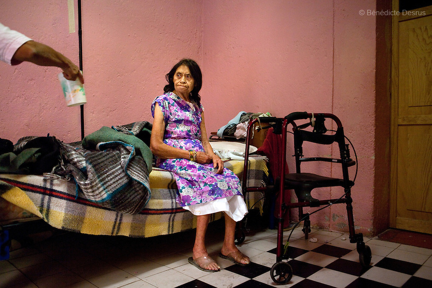 Reynita, a resident of Casa Xochiquetzal, sits on her bed at the shelter in Mexico City, Mexico on October 9, 2010. Reynita found out she has cancer, and has been depressed since the diagnosis, which she refuses to believe. Casa Xochiquetzal is a shelter for elderly sex workers in Mexico City. It gives the women refuge, food, health services, a space to learn about their human rights and courses to help them rediscover their self-confidence and deal with traumatic aspects of their lives. Casa Xochiquetzal provides a space to age with dignity for a group of vulnerable women who are often invisible to society at large. It is the only such shelter existing in Latin America. Photo by Bénédicte Desrus