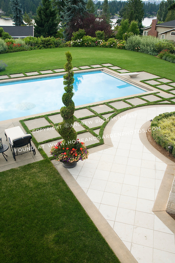 An overhead view looking down on half of a beautifully manicured, poolside landscape featuring lush green grass lawn, a border of mixed annuals, perennials and grasses, a beautiful blue swimming pool with diving board, a geometric pattern of concrete pavers and wide grass edging strips to set off the pool, and a dramatic pot of curly evergreen topiary and summer annuals all with a water view in the short distance in this Northwest summer scene in a suburban community east of Seattle.