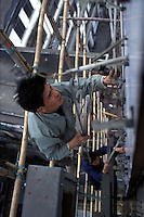 A migrant worker climbs scaffolding on a Calsberg neon sign next to the Pearl River in Guangzhou.