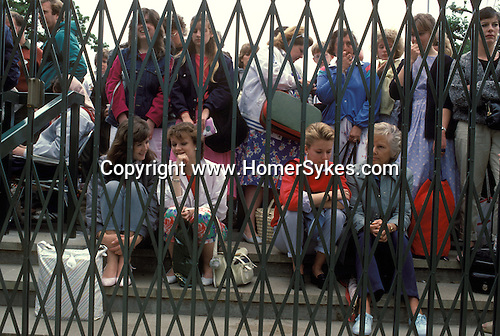 Tennise at Wimbledon, fans wait to be allowed in to gets tickets.  The English Season published by Pavilon Books 1987