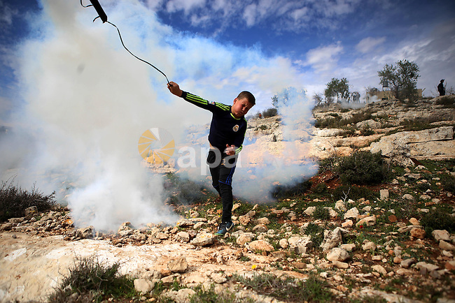 A Palestinian youth uses a sling shot to hurl back a tear gas canister at Israeli troops during clashes at a weekly protest against Jewish settlements, in the West Bank village of Nabi Saleh, near Ramallah February 6,2015. Photo by Shadi Hatem