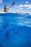 A woman kayaking over the sandy bottom of the ocean amid a pod of spinner dolphins, West O'ahu