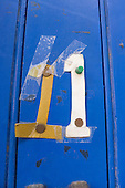 Spitalfields, London. Pinned and taped cardboard numbers, number eleven 11, on a blue painted panelled door.