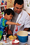 Inaki 4 years old w. father, cooking, baking in kitchen using teaspoon to put ingredient in batter