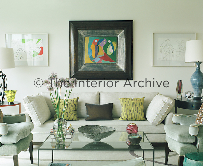 In this living room the sofa and chairs are covered in contrasting velvet and linen but in a similar tone of muted silver-grey providing a pleasing setting for framed prints and paintings and a collection of contemporary glass and ceramics