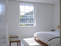 The all-white bedroom has a white cedar bed and a calm atmosphere
