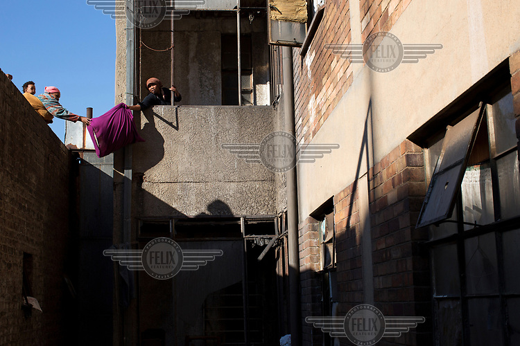 A woman passes her possessions out of a building on Bree Street that was in th eprocess of being cleared of squatters by the Red Ants. The Red Ants are a controversial private security company often hired to clear squatters from land and so-called 'hijacked' properties.