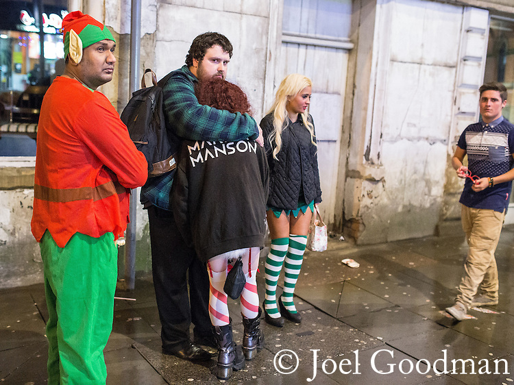 © Joel Goodman - 07973 332324 . 21/12/2013 . Manchester , UK . A man hugs a woman wearing a Marilyn Manson sweatshirt next to a man dressed as an elf . Christmas revellers out in the rain in Manchester on Mad Friday , the last Friday night before Christmas which is typically one of the busiest nights of the year for police and ambulance crews . Photo credit : Joel Goodman