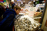 A visitor looks over a selection of clams at Pike Place Fish Company  in Seattle.  For over a century a century, the Pike Place Market, has become a city institution and a national attraction, bringing in over a million tourists a year. .Jim Bryant Photo. ©2010. ALL RIGHTS RESERVED.