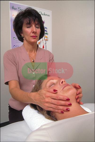 therapist aligning patient's chakra during Reiki massage