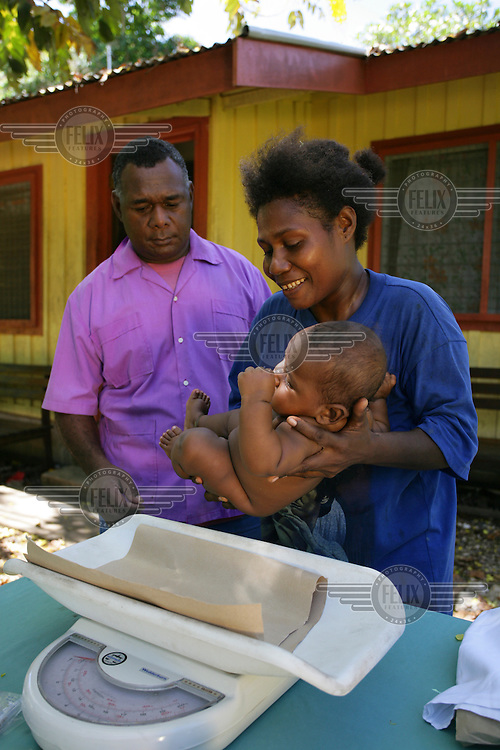 6 month old Ladi is lowered on to scales to moniter growth at the Kakabona clinic in Honiara.