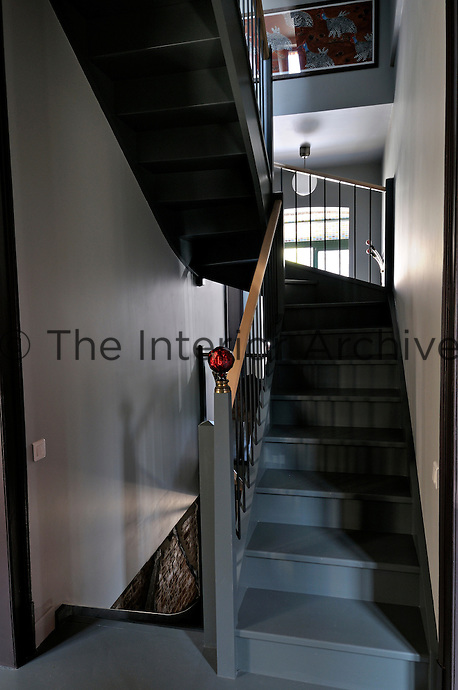 A contemporary grey-painted staircase forms part of the recent restoration of the house