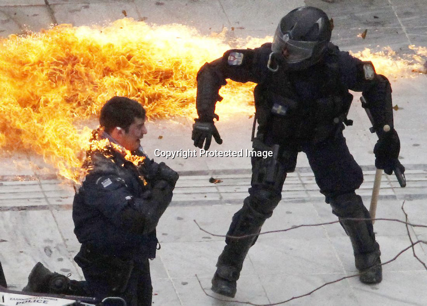 "A motorcycle policeman burns as his colleague, left, tries to help him after protesters threw a petrol bomb in Athens, Wednesday, Feb. 23, 2011. ""Caught On Fire"" (Dimitri Messinis/The Associated Press)"