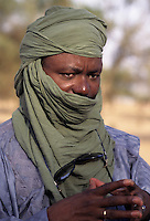 Akadaney, Niger.  Fulani Man wearing a Tuareg Tagelmust, or Veil, and an Embroidered Boubou.  This is an example of how one culture, the Fulani, in close contact with another, may adopt the other's clothing styles.