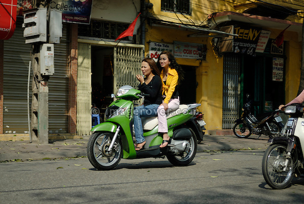 Asia, Vietnam, Hanoi. Hanoi old quarter. Two tarted up vietnamese woman riding on motorbike through Hanoi.
