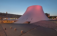 Le Volcan or the Volcano at night, illuminated in pink, auditorium opened 1982, designed by Oscar Niemeyer, 1907-2012, and Jean-Maur Lyonnet, at the Maison de la Culture du Havre, Le Havre, Normandy, France. Behind are apartment buildings designed by Auguste Perret, 1874-1954, who led the reconstruction of Le Havre in the 1950s, after the town was completely destroyed in WWII. The large volcano shown here contains a 1200 seat theatre and 350 seat cinema, while the small volcano has a 500 seat hall and 80 seat auditorium and is now used as a reference library. The forum is built from concrete and the buildings are linked and accessed via ramps. The centre of Le Havre is listed as a UNESCO World Heritage Site. Picture by Manuel Cohen