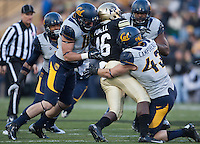 California defenders' Lucas King and Dan Camporeale tackle Colorado tailback Christian Powell during the game during the game against Colorado at Folsom Field in Boulder, Colorado on November 16th, 2013.  Colorado defeated California, 41-24.
