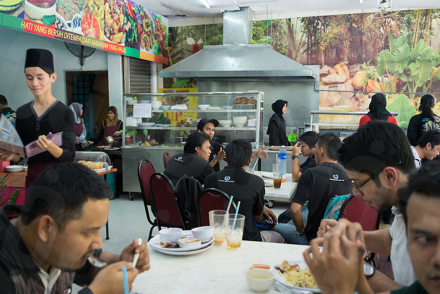 January 15, 2015 - Kuala Lumpur (Malaysia). Customers in one of the several restaurants owned by Global Ikhwan in the capital Kuala Lumpur. The enterprise, which employs 4,000 people worldwide through its complicated network of subsidiaries,operates restaurants, clothing shops, noodle factories and health clinics - just to name a few. It also runs its own schools, care homes and rehabilitation centres. © Thomas Cristofoletti / Ruom