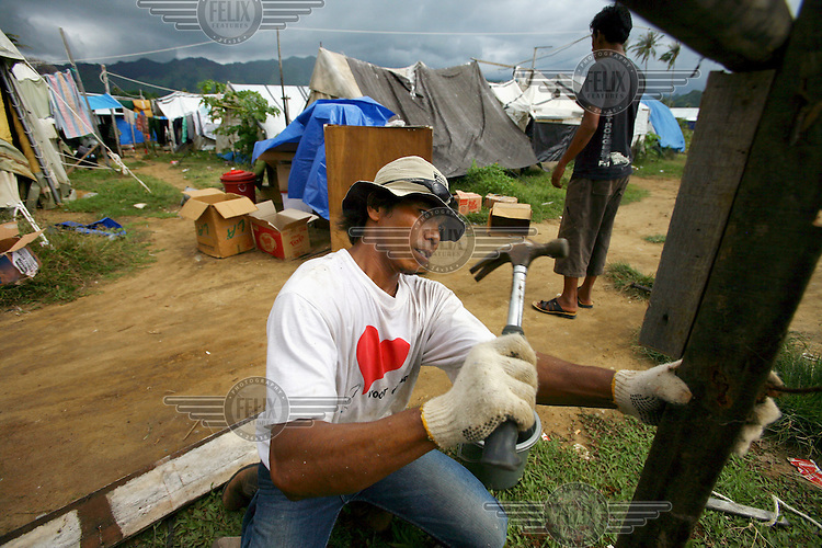 One year after the tsunami, Marzuki Juned, works to improve his tent at Lamkruet, just outside of Banda Aceh.