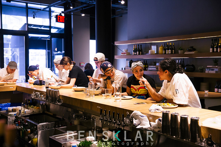 4:23pm<br /> <br /> The kitchen staff sits at the bar catching up and having family meal before dinner service begins.
