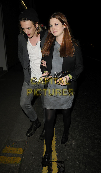 "JAMIE CAMPBELL BOWER & BONNIE WRIGHT.The ""Cherrybomb"" VIP screening, Beaufort House, London, England..April 20th, 2010.full length black blazer jacket tights sandals shoes white top jeans denim boots arms linked couple jaime grey gray dress hat tattoo.CAP/CAN.©Can Nguyen/Capital Pictures."