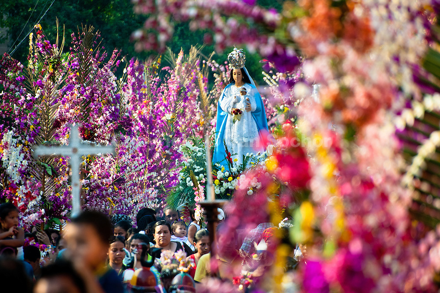 """An altar with a statue of Virgin Mary is carried during the procession of the Flower & Palm Festival in Panchimalco, El Salvador, 8 May 2011. On the first Sunday of May, the small town of Panchimalco, lying close to San Salvador, celebrates its two patron saints with a spectacular festivity, known as """"Fiesta de las Flores y Palmas"""". The origin of this event comes from pre-Columbian Maya culture and used to commemorate the start of the rainy season. Women strip the palm branches and skewer flower blooms on them to create large colorful decoration. In the afternoon procession, lead by a male dance group performing a religious dance-drama inspired by the Spanish Reconquest, large altars adorned with flowers are slowly carried by women, dressed in typical costumes, through the steep streets of the town."""