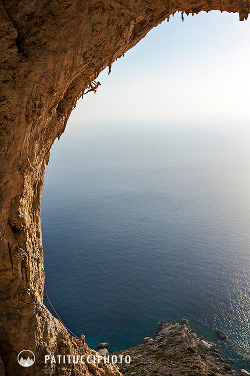 Woman climbing the wildly overhanging route Typhoon, 7c+, in the enormous and difficult Crystal Cave, Telendos, Kalymnos, Greece.