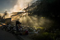A man fossicks through roadside garbage to extract plastic to be sold for recycling on November 20, 2017 in Port-au-Prince, Haiti. <br /> Photo Daniel Berehulak for The New York Times