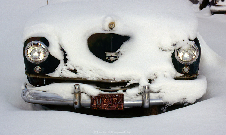 An old Kaiser automobile from the 1950's lies buried in snow.