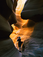 A Photographer captures the beauty of the sandstone Lower Antelope slot canyon in the desert landscape near Page, Arizona