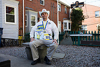 Carlos Arredondo, 57, sits in his front yard in Roslindale, Boston, Massachusetts, USA, on Sat., March 31, 2018. Arredondo is well known as the &quot;man in the cowboy hat&quot; who helped out in the aftermath of the Boston Marathon Bombing in 2013. Carlos is wearing a jacket that he has used to create a t-shirt design for when he runs the Boston Marathon later this year. Though he has run the race unofficially previously, this will be the first time he runs it &quot;legally,&quot; he says.<br /> <br /> Behind the Carlos is a memorial to his two sons,  Marine Lance Corporal Alexander Scott Arredondo and Brian Arredondo. Alex was killed while serving in Iraq in 2004, and Brian died by suicide in 2011.