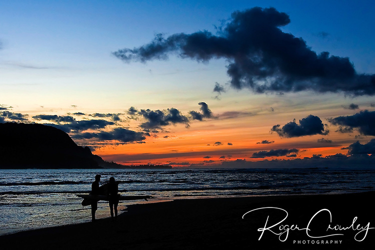 A couple of surfers head home in the sunset on Ke'e Beach at Hanalei Bay on the island of Kaua'i, Hawaii.