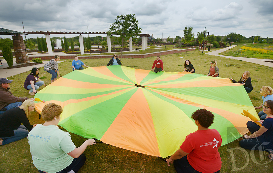 NWA Democrat-Gazette/BEN GOFF @NWABENGOFF<br /> Staff from the Bentonville Public Schools Adventure Club program play a parachute game on Thursday May 19, 2016 during a staff development outing at Orchards Park in Bentonville. The staff members were learning games and activities to share with students in the before and after school program for kindergarten through 6th graders.