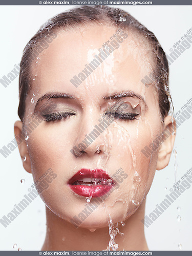 Closeup beauty portrait of a woman face with red lipstick and makeup with water running over it. Isolated on white background.