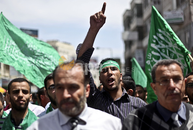 Palestinian Hamas supporters rally in the streets of the West Bank city of Ramallah to celebrate on May 6, 2011 the political unity reconciliation deal between the Islamic group and the Fatah movement which was signed by the two rival groups in Cairo the previous day. Photo by Issam Rimawi