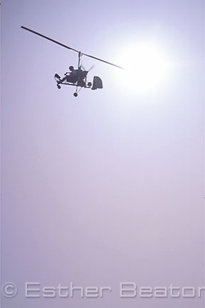 A gyrocopter in flight against sun. outback New South Wales