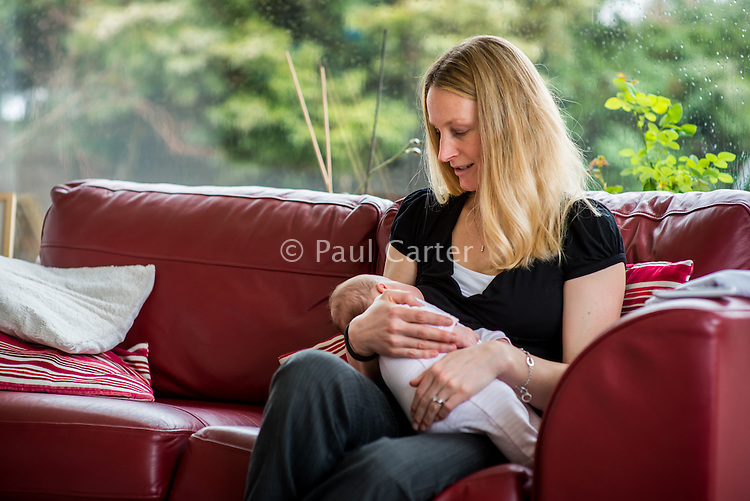 A woman sitting on her living room sofa and breastfeeding her 2 month old baby daughter.<br /> <br /> Hampshire, England, UK<br /> 10/02/2013