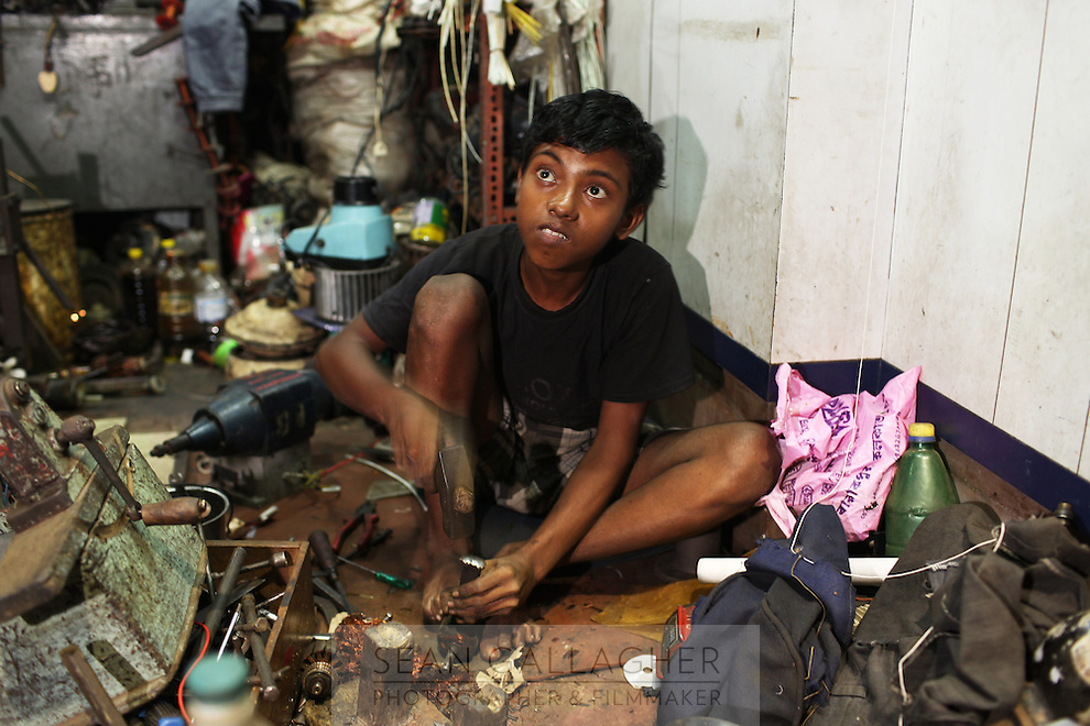 A boy working in a store in the Chandni Chowk electronics market in Kolkata, India. November, 2013
