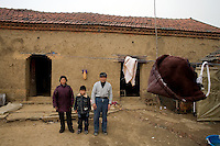 Grandparents Li Mao Rong (left) and Yan Cheng Shan pose for a portrait with their orphan grandson Yan Jing Ya outside their home in Yi Ling Village, Gangyun County, Jiangsu Province, China.  The boy's father died in a coal mining accident and his mother, who had been purchased for a dowry for marriage from the remote Yunnan Province, remarried after the death and abandoned the child.  The boy's grandparents can no longer support the boy...At the time of the picture, China's Amity Foundation charity, was investigating the family's situation in preparation to raise money to financially support these children and other orphans in similar situations.  With Amity's support, each orphan, aged 6-12, would receive approximately 1,400 RMB annually (about 200 USD) to pay for the cost of living. Amity works to keep children out of the institutional orphanages in China, preferring to provide monetary assistance that can help maintain a family environment for the orphans it helps.