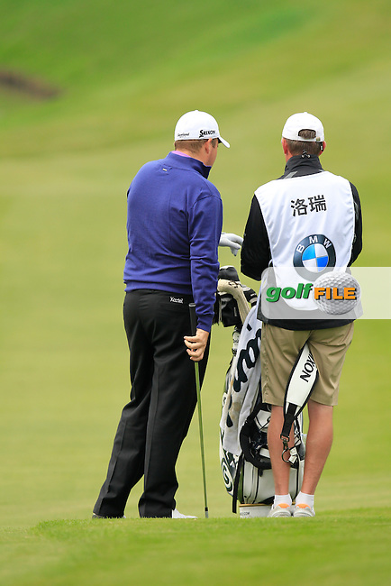 Shane Lowry (IRL) and caddy Dermot Byrne prepare to play his 2nd shot on the 13th hole during Friday's Round 2 of the 2013 BMW Masters presented by SRE Group held at Lake Malaren Golf Club, Shanghai, China. 25th October 2013.<br /> Picture: Eoin Clarke/www.golffile.ie