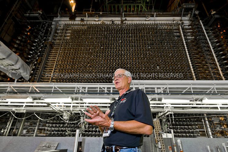 8/28/2008--Hanford, WA, USA..Robert Egge gives a tour in front of the core of the B-Reactor at the Hanford Site, Washington, along the banks of the Columbia River. The reactor was the first large scale plutonium production reactor ever built and started production in December, 1944. The project was commissioned under the Manhattan Project, during World War II, to develop the first nuclear weapons. The B-REactor was shut down in 1968 and on August 25th, 2008, was declared a National Historic Landmark and is now open to tourists...The reactor was graphite moderated and water cooled. It consisted of a 28 by 36-foot, 1,200-ton graphite cylinder lying on its side, penetrated through its entire length horizontally by 2,004 aluminum tubes, the ends which can be seen here. Two hundred tons of uranium slugs the size of rolls of quarters and sealed in aluminum cans went into the tubes...During the Cold War, the Hanford project was expanded to include nine nuclear reactors and five massive plutonium processing complexes, which produced plutonium for most of the 60,000 weapons in the U.S. nuclear arsenal. The weapons production reactors were decommissioned at the end of the Cold War, but the manufacturing process left behind 53 million U.S. gallons of high-level radioactive waste that remains at the site. Hanford is the most contaminated nuclear site in the United States and is the focus of the nation's largest environmental cleanup, providing thousands of jobs to residents in nearby towns such as Richland...©2008 Stuart Isett. All rights reserved.