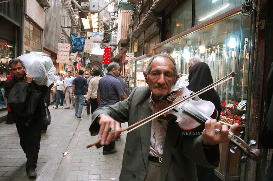 2005..Iran. Tehran. Violinist in the bazaar...Iran. Téhéran. Violoniste dans le souk.