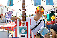 Hmong man age 21 wears decorative sunglasses sells CD music disks.  Hmong Sports Festival McMurray Field St Paul Minnesota USA