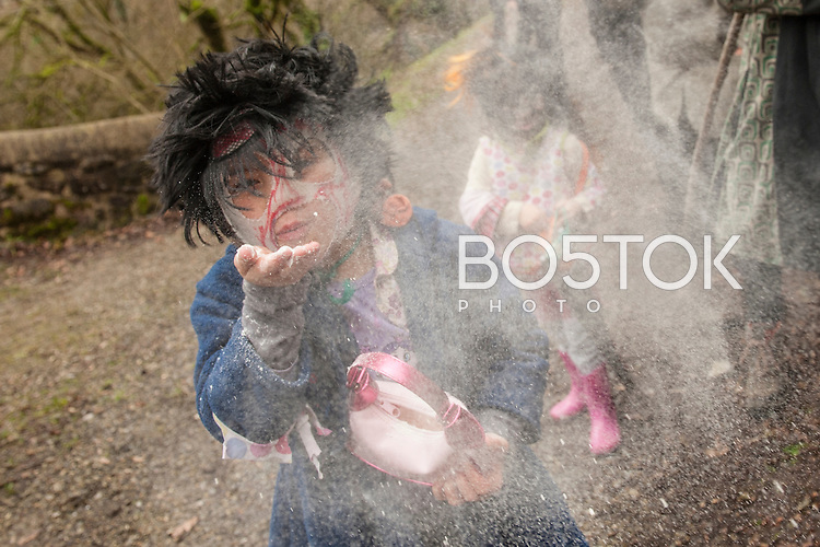 "A little girl throws flour during the celebration of an ancient traditional carnival. Ituren (Basque Country). February 1, 2016. The ""Joaldunak"" (""those who play the bell"") is a character that takes part in the carnival at the villages of Ituren and Zubieta carrying sheep furs and big cowbells tied to their backs to wake up the earth, looking for a good new year, a good harvest and to keep away the bad spirits.  (Gari Garaialde / BostokPhoto)"