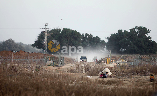 Palestinian protesters take cover in front of an Israeli military vehicle during clashes with Israeli troops near a border fence between Israel and the Gaza Strip on October 14, 2015 east of Bureij in central Gaza. The outbreak of violence between Palestinians and Israeli forces in recent weeks has worsened in October, raising fears of a third intifada, or uprising. Photo by Ashraf Amra