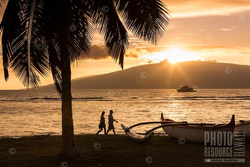 A visiting couple walks along on a Maui beach as the sun sets behind Lana'i.